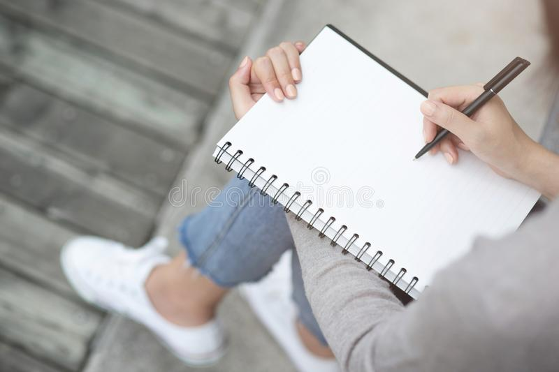 Close up hand young woman are sitting on a marble chair. using pen writing Record Lecture note pad into the book stock photography