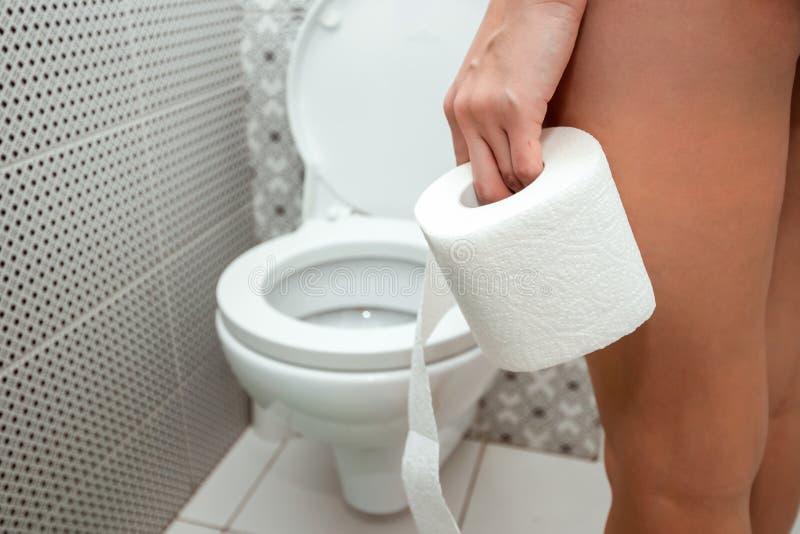 Close-up, handenduvushki, die een broodje van toiletpapier voor het toilet houden Het concept problemen met de darmen, royalty-vrije stock fotografie