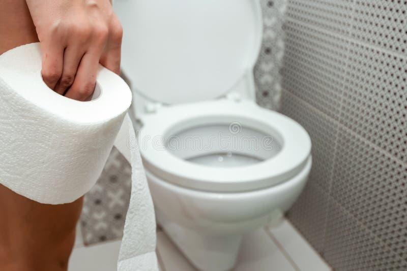 Close-up, handenduvushki, die een broodje van toiletpapier voor het toilet houden Het concept problemen met de darmen, stock afbeelding