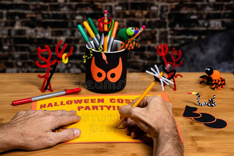 Close up of the hands of an adult male Doing crafts and Making a Party Sign for Halloween.  Several Halloween Craft decorations royalty free stock images