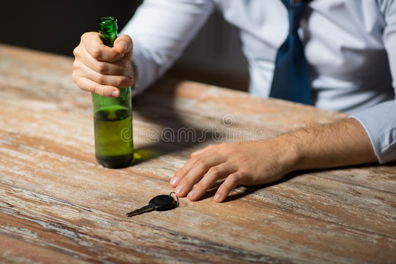 Close up of hands with alcohol and car key. Alcohol abuse, drunk driving and people concept - close up of male driver hands with beer bottle and car key on table royalty free stock photo