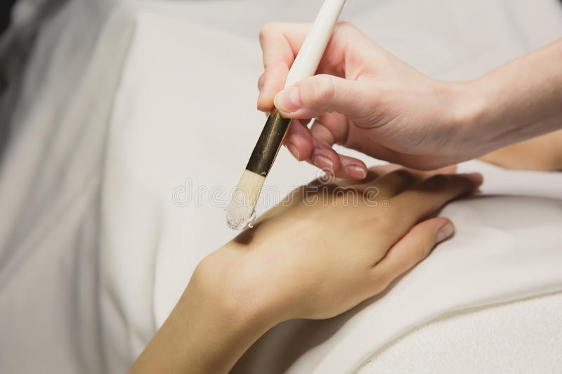 Close up of hands applying cream over table. SPA royalty free stock photography