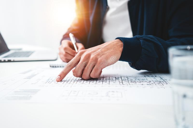 Close-up of hands architect uses laptop and building blueprint on working table in office space royalty free stock photo