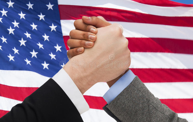Close up of hands arm wrestling over american flag. Partnership, politics, gesture and people concept - close up of two hands arm wrestling over american flag royalty free stock photography