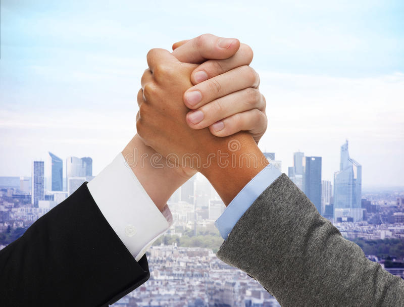 Close up of hands arm wrestling over city. Business competition, challenge, cooperation, people and partnership concept - concept - close up of hands arm royalty free stock image