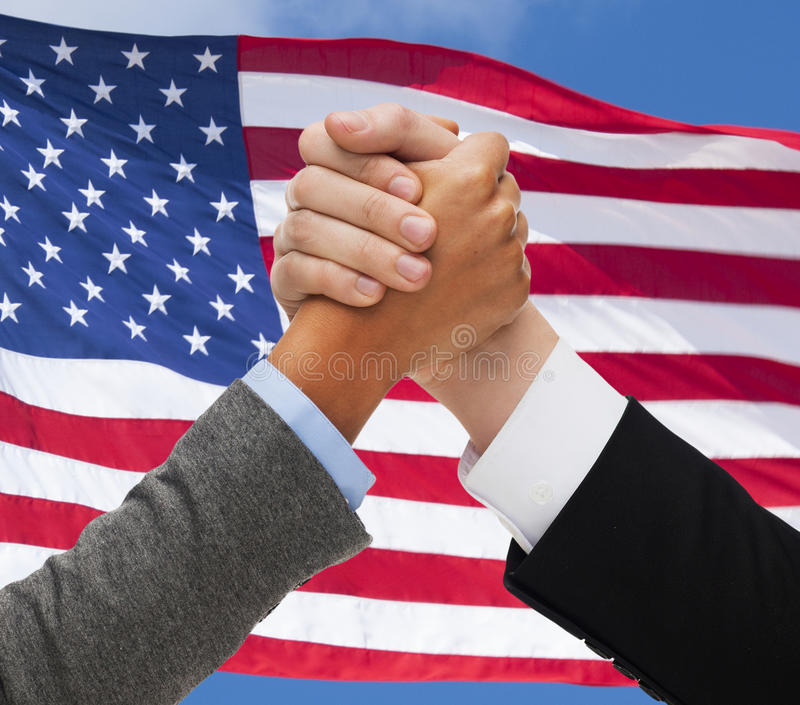 Close up of hands armwrestling over american flag. Partnership, politics, gesture and people concept - close up of two hands armwrestling over american flag stock photography