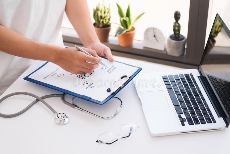 Close up on hands. Asian female doctor with laptop and writing something on clipboard, prescription, paperwork,patient checklist royalty free stock photo
