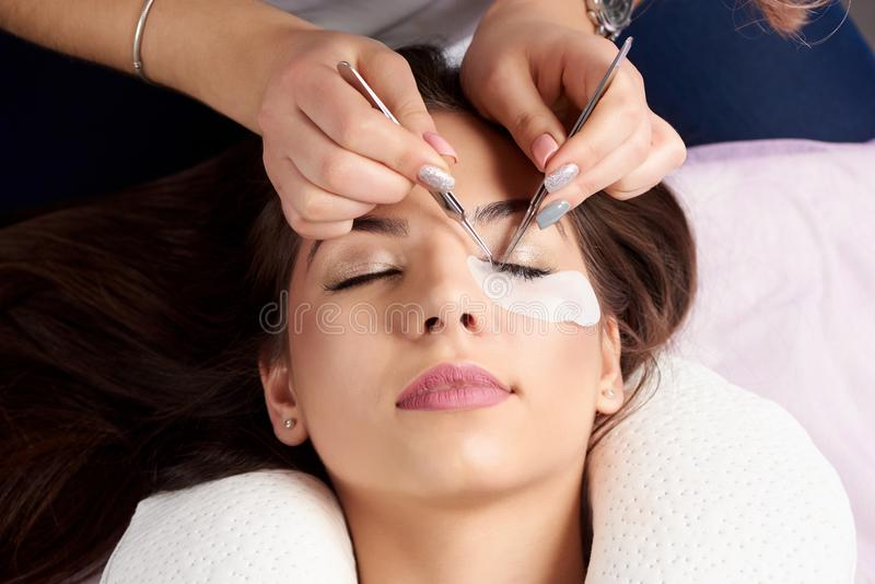 Close-up hands beautician with tweezers at process of eyelash extension royalty free stock photo