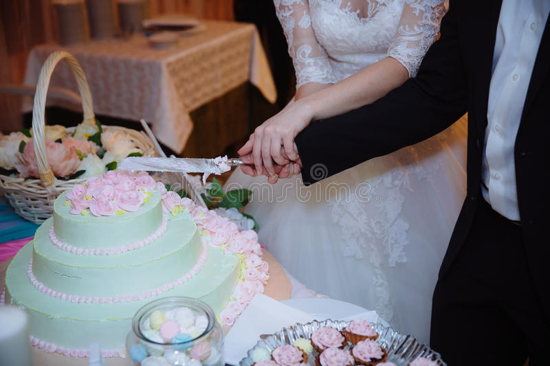 Close-up Hands of the bride and groom cut the wedding cake. Concept of candy shop stock photos