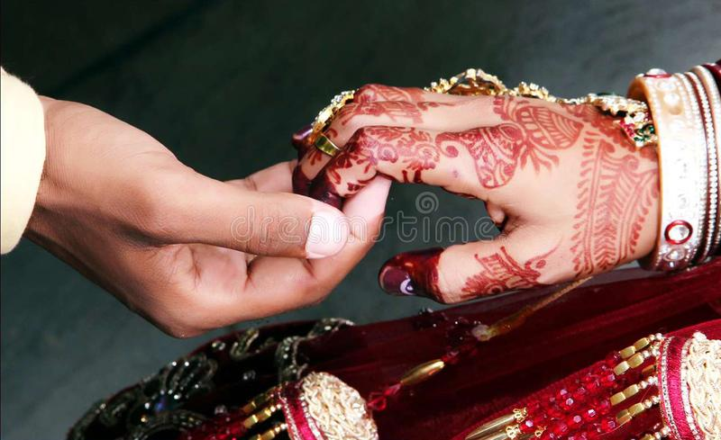 Close up of hands of bride and groom holding together at a traditional wedding. royalty free stock image