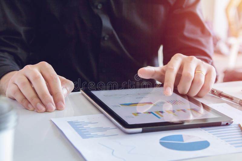 Close up hands business man in black shirt using tablet, point to discuss, plan and chart the rise and fall of the economy royalty free stock photo