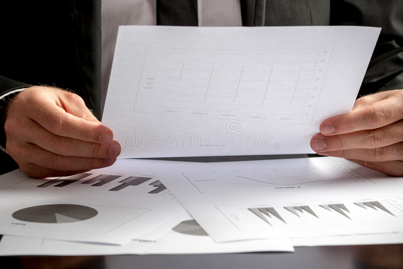 Close up of the hands of a businessman analysing a set of graphs royalty free stock photos