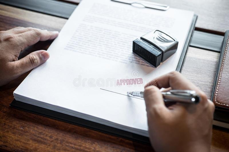Close up hands of businessman signing and stamp on paper document to approve business investment contract agreement stock photos