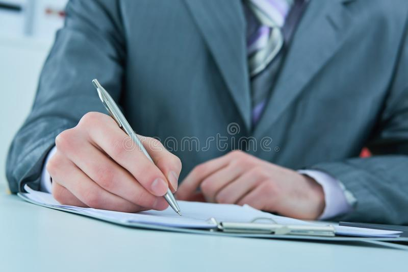 Close up of the hands of a businessman in a suit signing or writing a document on a sheet of white paper. Close up of the hands of a businessman in a suit royalty free stock images