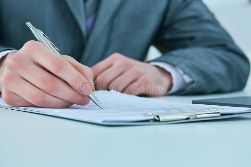 Close up of the hands of a businessman in a suit signing or writing a document on a sheet of white paper. Close up of the hands of a businessman in a suit stock photo