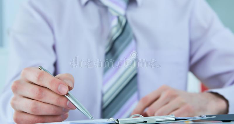 Close up of the hands of a businessman in a suit signing or writing a document on a sheet of white paper. Close up of the hands of a businessman in a suit stock image