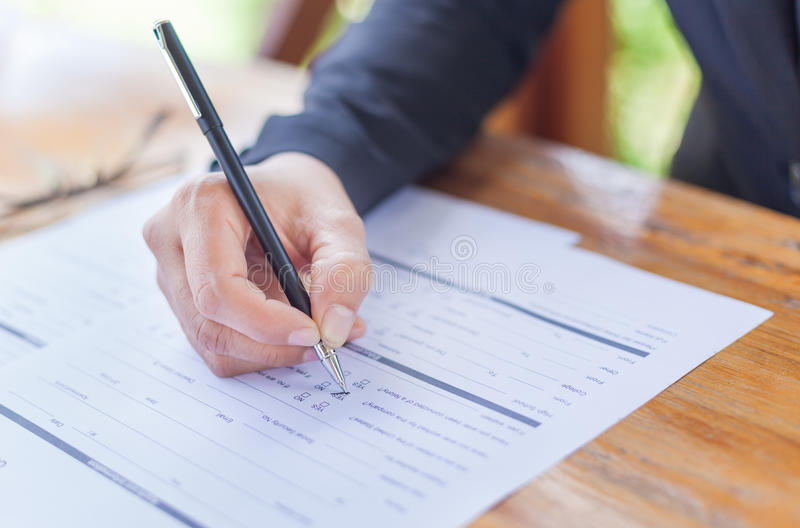 Close up of the hands of a businesswoman in a suit signing or writing a document on a sheet of white paper stock images