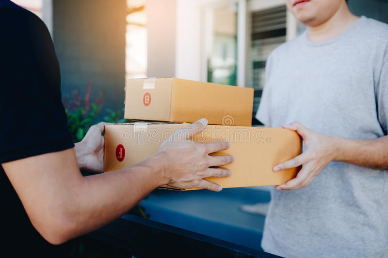 Close up of hands cargo staff are delivering cardboard boxes with parcels inside to the recipient`s hand.  royalty free stock photography