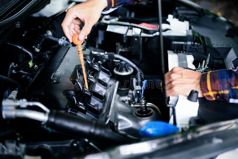 Close up hands checking lube oil level of car engine from deep-stick for service and maintenance concept stock image