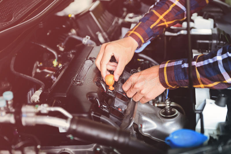 Close up hands checking lube oil level of car engine from deep-stick for service and maintenance concept vintage tone royalty free stock image
