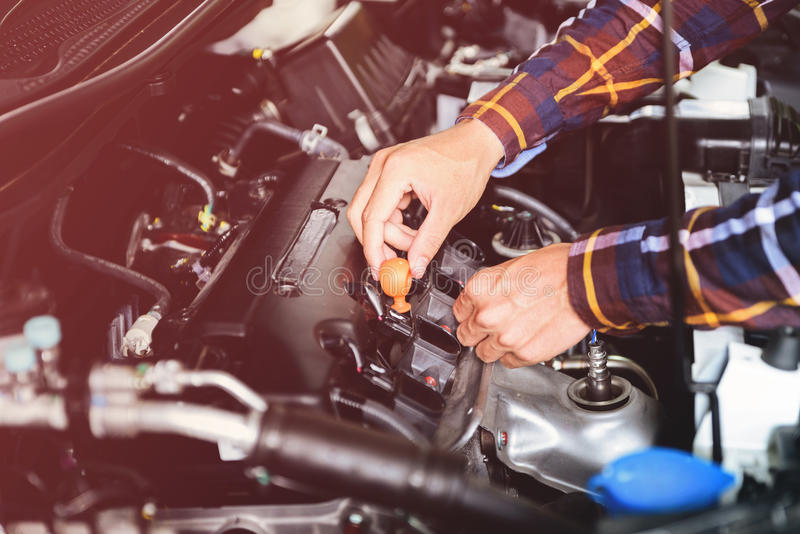 Close up hands checking lube oil level of car engine from deep-stick for service and maintenance concept vintage tone stock photography
