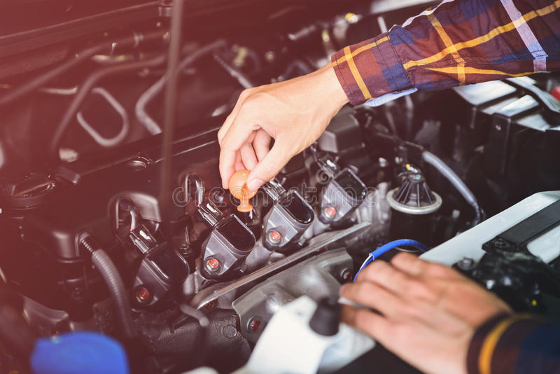 Close up hands checking lube oil level of car engine from deep-stick for service and maintenance concept vintage tone stock images
