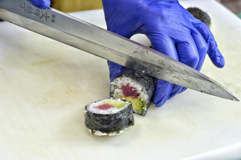 Close-up of the hands of a chef making sushi. stock photos