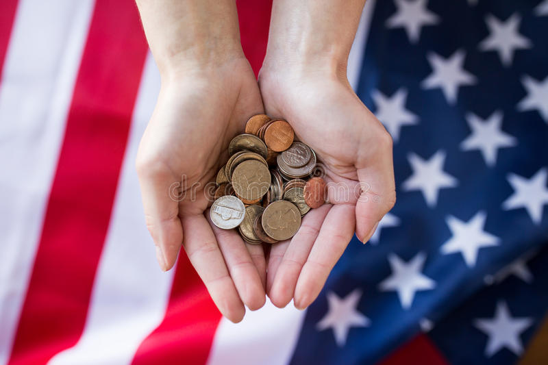 Close up of hands with coins over american flag. Finances, money, crisis, investment and state budget concept - ose up of hands with coins over american flag stock image