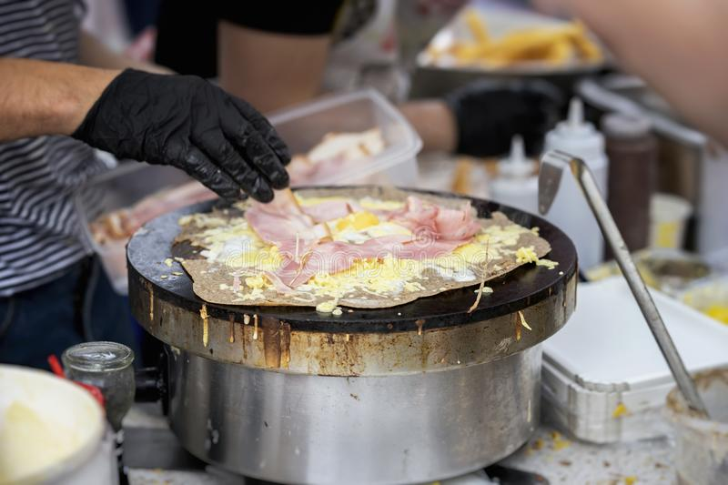 Hands of cook in gloves preparing crepe galette with ham, cheese and egg on black plate. Concept national food, very stock photo
