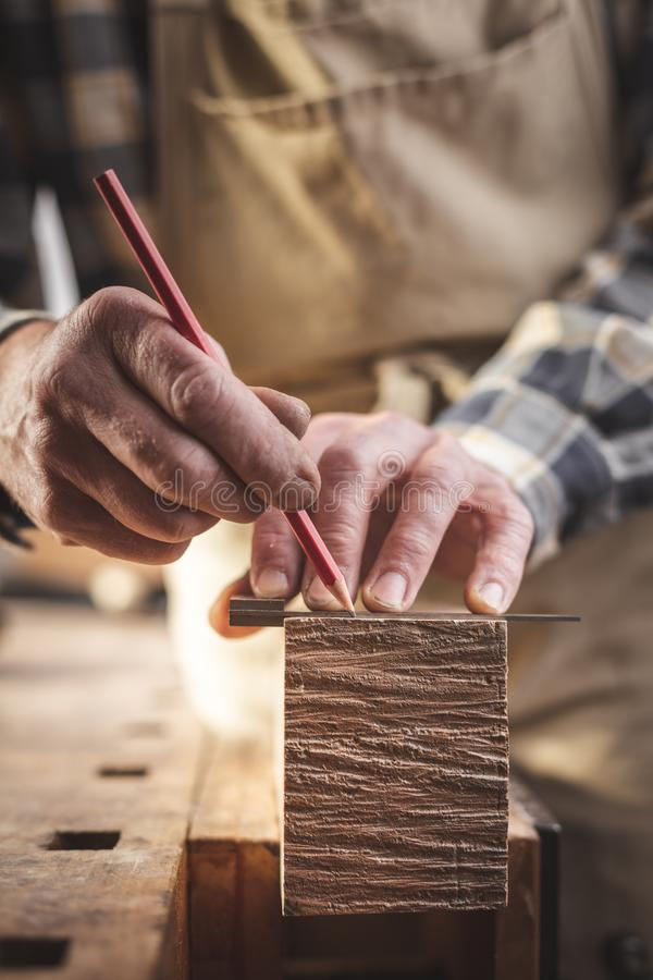 Craftsman marking a piece of wood with a pencil. Close-up of the hands of a craftsperson using a red pencil and an angle tool to mark a wooden strip royalty free stock photography