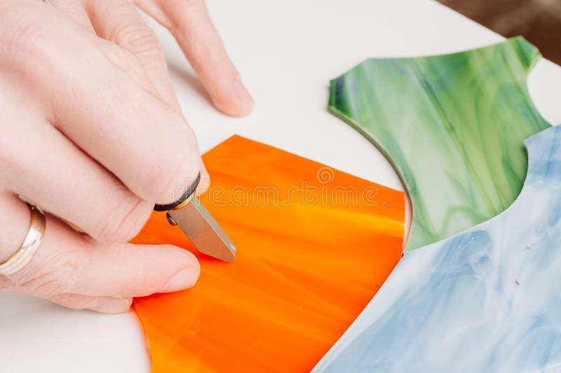 Close up hands cutting glass for stained glass into small mosaic. Squares stock photography