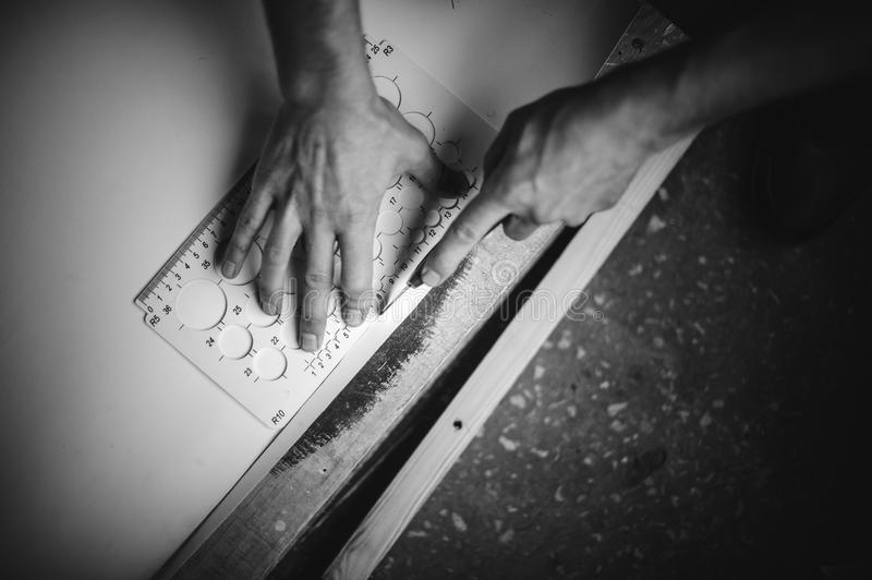 Close up of hands cutting paper with knife and ruler royalty free stock image