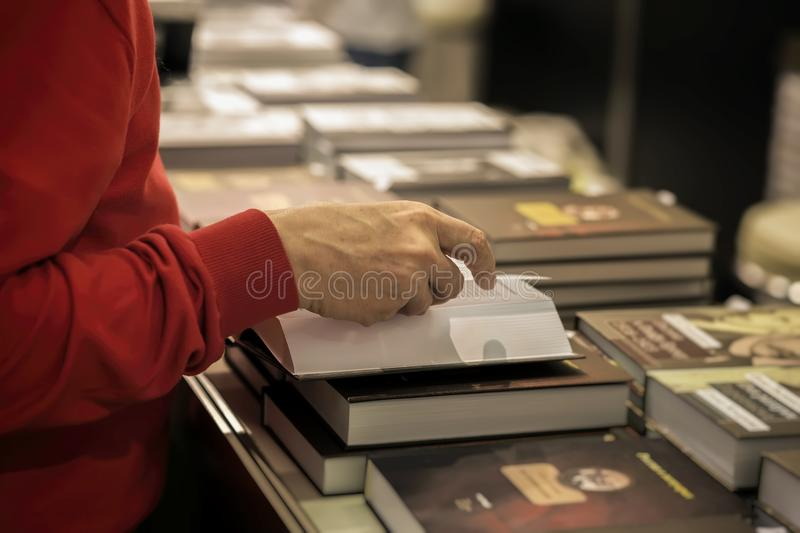 Close-up of hands of elderly person with open book, bookstore, library. Real scene. Education concept, Self-study. Close-up of hands of the elderly person with royalty free stock images