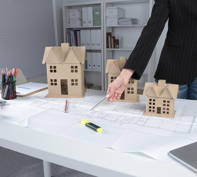Close-up of hands of female architects working on blueprint stock image