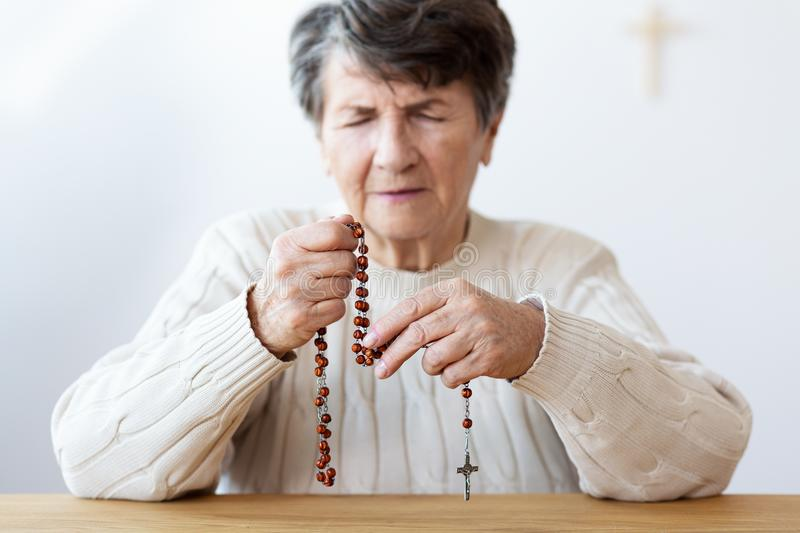 Close-up on the hands of a focused grandmother praying with a re stock photography