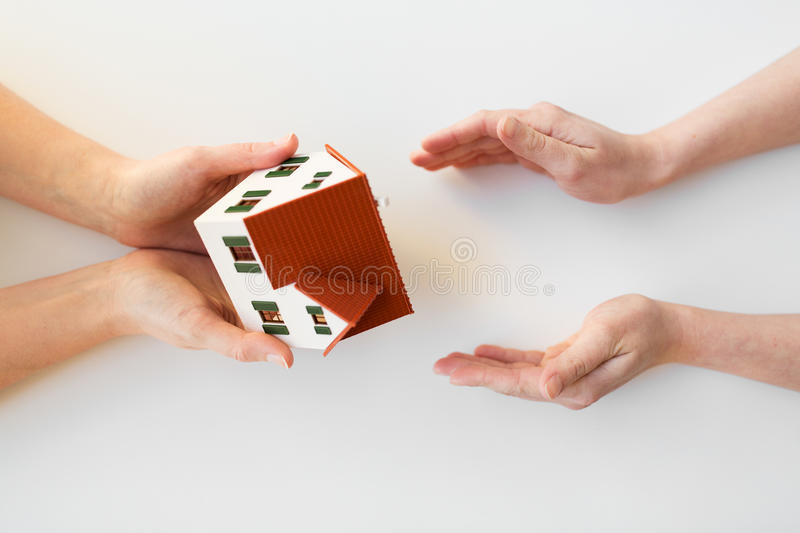 Close up of hands giving house or home model. Charity, building, sale, real estate and property concept - close up of hands giving and receiving house or home stock photos