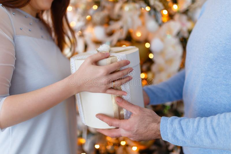 Close-up of hands and Happy young man and woman, giving each other gifts. Merry Christmas and happy New year!. A young couple royalty free stock photo