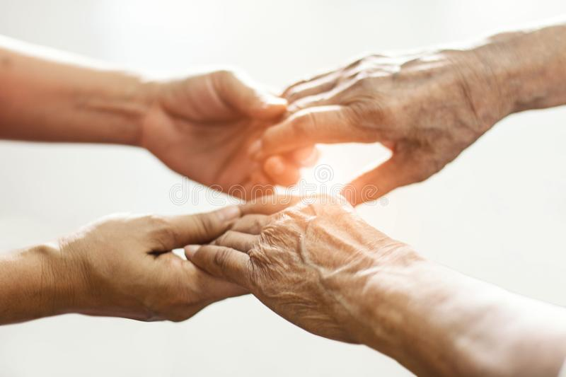 Close up hands of helping hands elderly home care. Mother and daughter stock photo