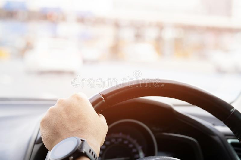 Close up of hands hold steering wheel young man driving a car royalty free stock photos