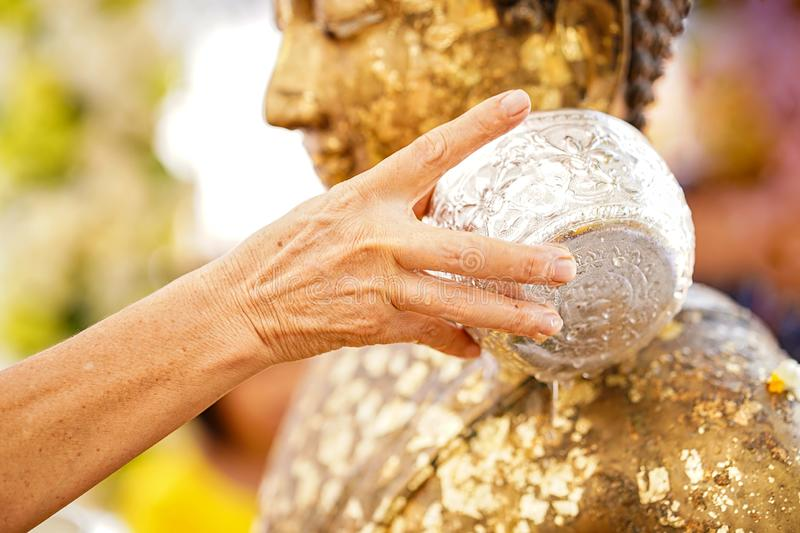Close-up Hands holding a bowl of water to pour Buddha in the Songkran tradition. Hands of thai people pouring water bathing on stock image