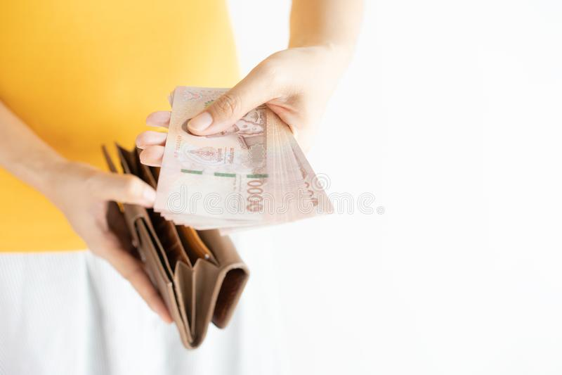 Close up hands holding cash and open brown leather wallet. Left hand pulling Thailand money Bahtand right hand holding wallet royalty free stock photos