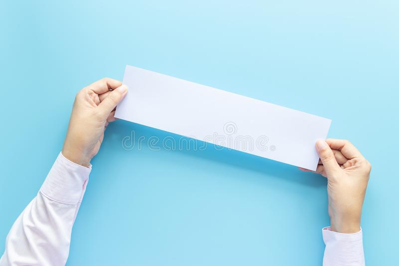Close up hands holding empty white blank horizontal paper for flyer or invitation mock up isolated on a blue background. royalty free stock photos