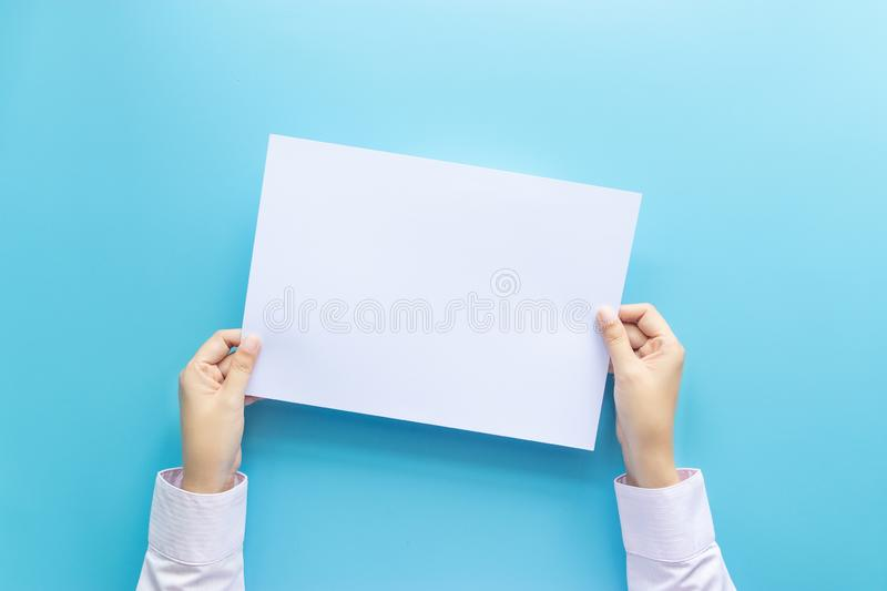 Close up hands holding  empty white blank letter paper for flyer , presentation or invitation mock up isolated on a blue. Background stock images