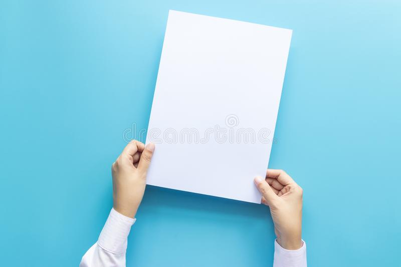 Close up hands holding  empty white blank letter paper size A4 for flyer or invitation mock up isolated on a blue background. stock photo