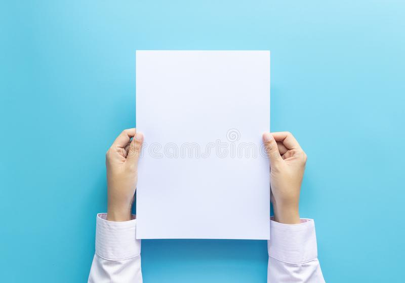 Close up hands holding  empty white blank letter paper size A4 for flyer or invitation mock up isolated on a blue background.  stock images