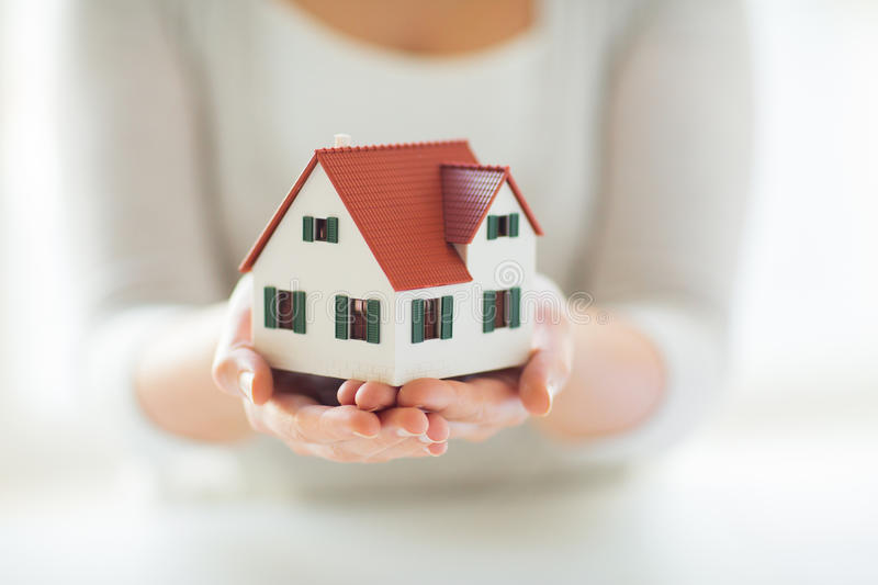 Close up of hands holding house or home model. Architecture, building, construction, real estate and property concept - close up of hands holding house or home stock photography