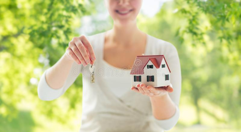 Close up of hands holding house model and keys. Mortgage, real estate and property concept - close up of hands holding house model and home keys over green royalty free stock photos