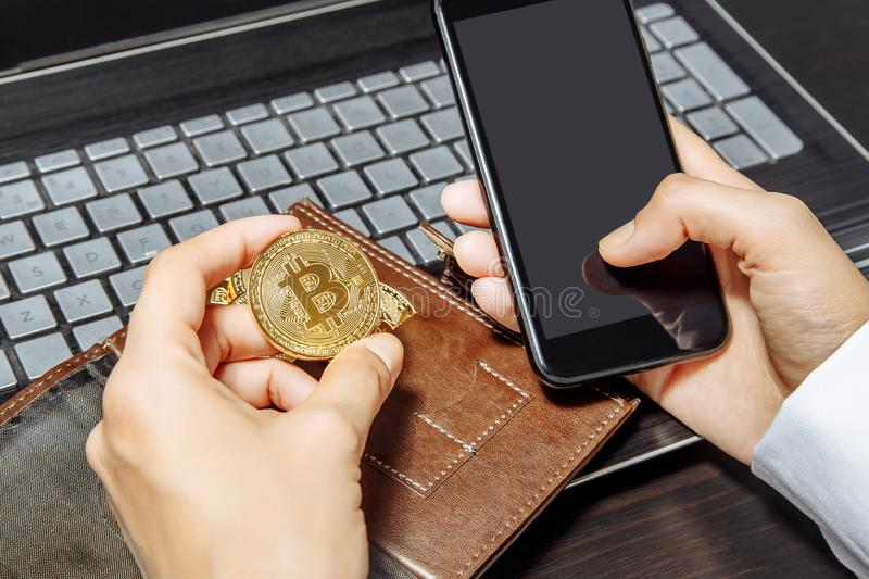 Close-up of hands holding smartphone and bitcoin. Crypto currency concept. Financial transaction.  stock photography