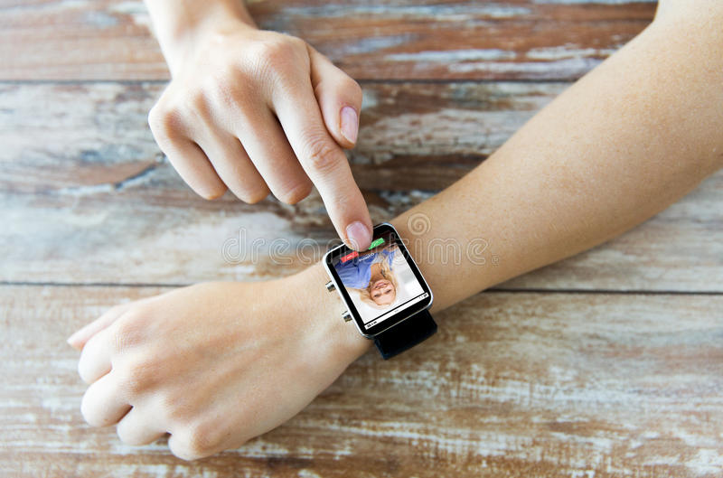 Close up of hands with incoming call on smartwatch. Business, modern technology, communication and people concept - close up of female hands setting smart watch stock photos