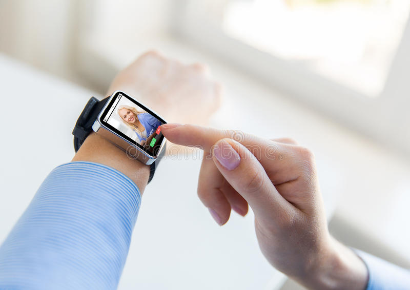 Close up of hands with incoming call on smartwatch. Business, modern technology, communication and people concept - close up of female hands setting smart watch royalty free stock image